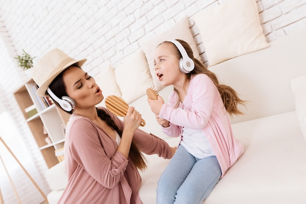 Girl and woman in headphones singing at home.