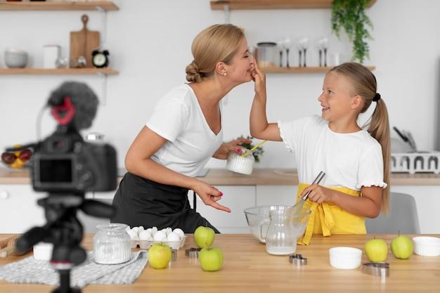 Ragazza e donna che tengono le uova colpo medio