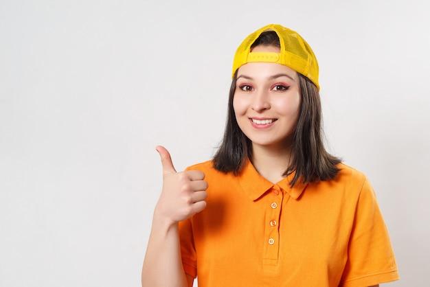 明るいポロシャツの女の子女性は親指ジェスチャーと笑顔を示しています