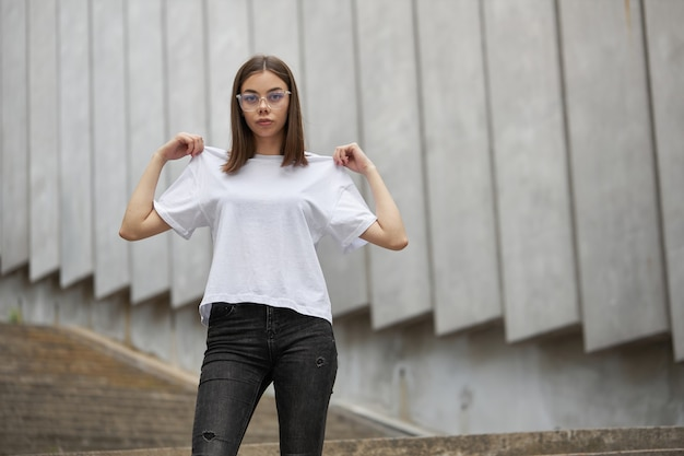 Girl or woman wearing white blank t-shirt with space for your logo, mock up or design in casual urban style