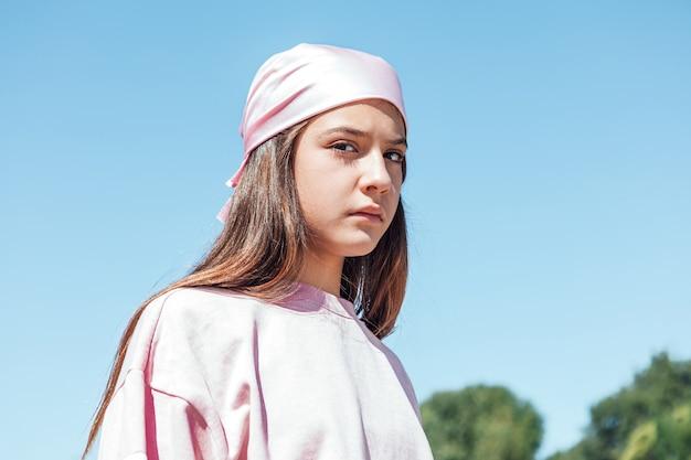 Девушка женщина с розовым платком на голове, с грустным жестом. международный день борьбы с раком груди на фоне неба.