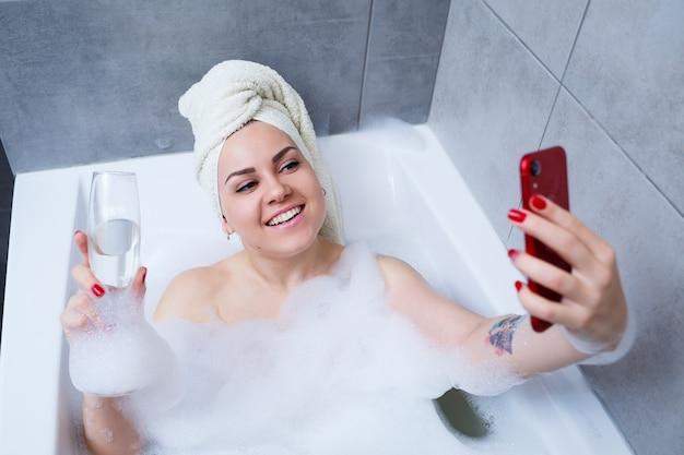 頭にタオルを持った女の子の女性は、白いバスタブにシャンパングラスを持って横になり、電話で自分撮りをします。彼女の手にはたくさんの酔った石鹸があります。忙しい一日を過ごした後はリラックスしてください。スパリラックス手順