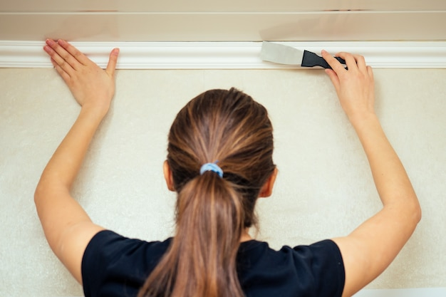 Girl (woman) working in a black t-shirt is installing a plinth on the ceiling
