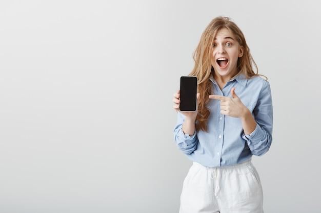 Девушка выиграла смартфон в лотерею. портрет удивленной очаровательной молодой женщины в синей блузке, показывающей смартфон и указывающей на устройство указательным пальцем, отвисшей челюстью, кричащей от волнения и удивления