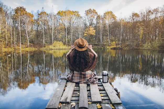 Girl on a wooden old bridge on a lake