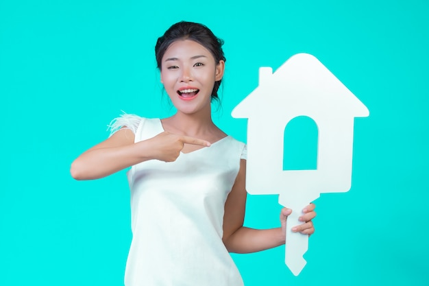 The girl wore a white long-sleeved shirt with floral pattern, holding the house symbol and showing various gestures with a blue .