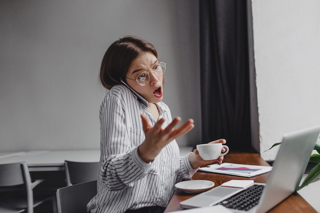 Girl worker in glasses emotionally and indignantly talking on phone, sitting in office with laptop and cup of coffee.