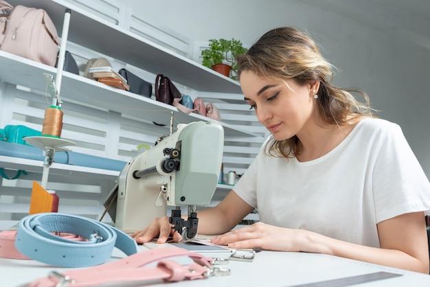 Девушка-работник шьет на швейной машине