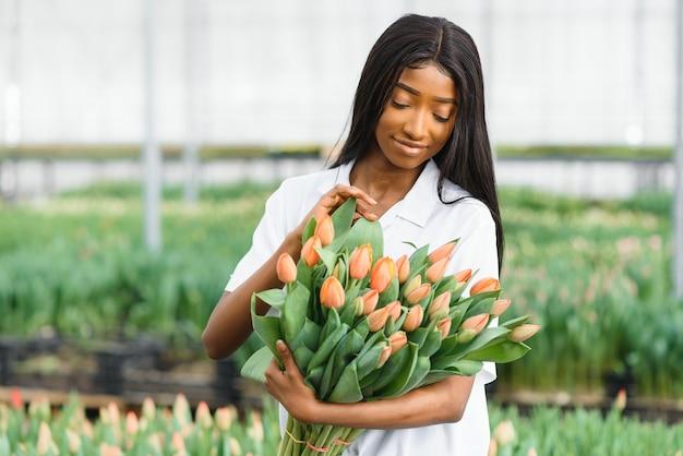 Девушка, рабочий с цветами в теплице