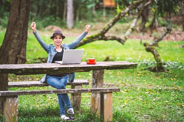 作業と休暇の休日の時間に森のテーブルの上のコーヒーを飲みながらの女の子