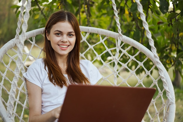 Девушка работает на природе с ноутбуком и смотрит в камеру
