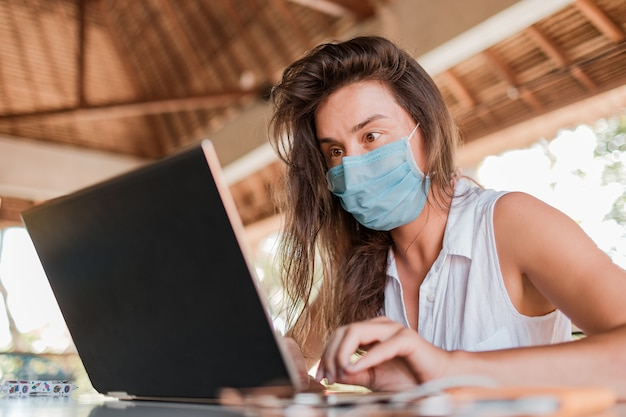 Girl working on laptop in a mask.  high quality photo