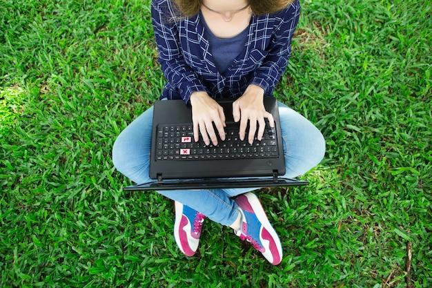 노트북에서 작업 하 고 잔디에 앉아 여자