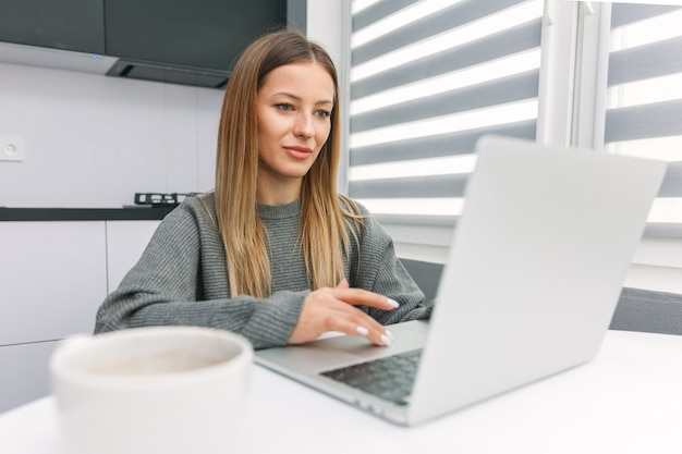 Девушка работает на ноутбуке за столом