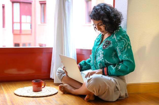 自宅からノートパソコンで作業している女の子、または自宅やフリーランサーから勉強している学生。