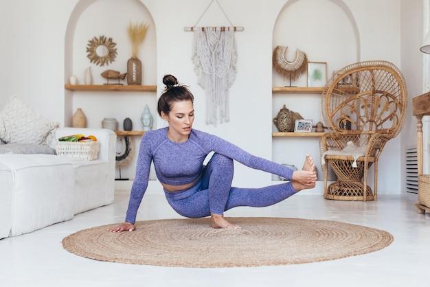 Девушка работает дома, делая передовые упражнения йоги.