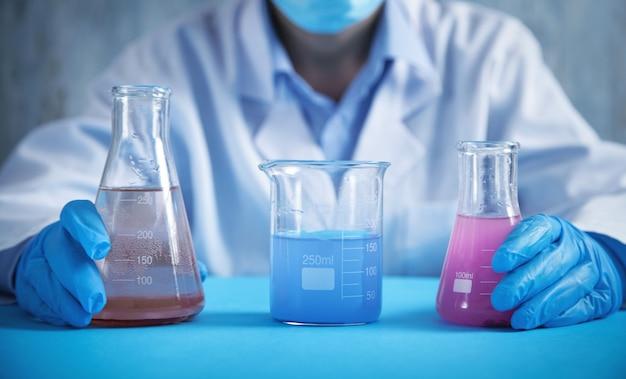 Девушка работает с колбами в лаборатории.