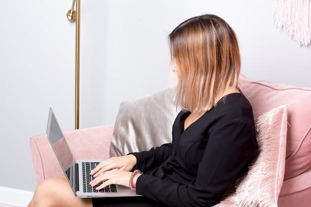 女の子はピンクのインテリアの側面図でピンクのアームチェアに座っているラップトップで働いています