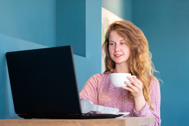 소녀는 노트북을 위해 작동합니다. 원격 작업, 온라인. 커피 한잔과 함께 카페에서 여자