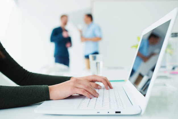 女の子はオフィスでラップトップで動作します。インターネットの共有と相互接続の概念