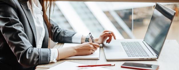 소녀는 직장에서 노트북에서 작동합니다. 성공적인 비즈니스 우먼은 스타트업을 만들고 결정을 내립니다.