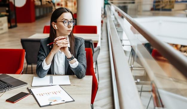 Девушка работает на ноутбуке на рабочем месте. успешная бизнес-леди создает стартап и принимает решения.