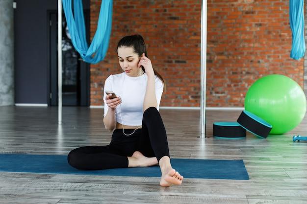 여자는 체육관에서 운동 후 또는 운동하기 전에 그녀의 스마트 폰으로 작동합니다.