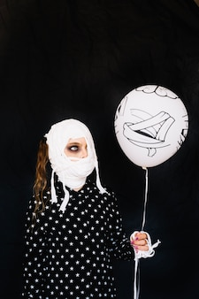 Girl wrapped in bandage with balloon