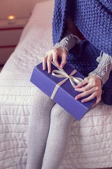 격자 무늬에 싸여있는 소녀는 침대에 앉아있는 동안 선물을 엽니 다.
