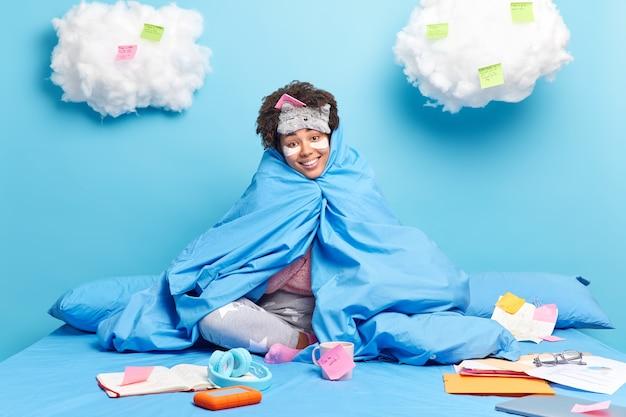 Girl wrapped in warm blanket applies collagen patches under eyes to reduce wrinkled poses on bed while doing home assignment isolated on blue