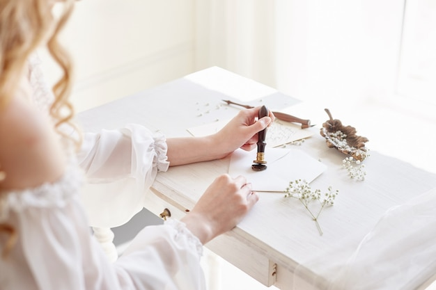 소녀는 그녀의 사랑하는 남자에게 편지를 씁니다. 집에 하얀 빛 드레스, 순수함과 순수함으로 테이블에 앉아 있습니다. 곱슬 금발의 낭만적 인 표정, 아름다운 눈. 테이블에 흰 야생화