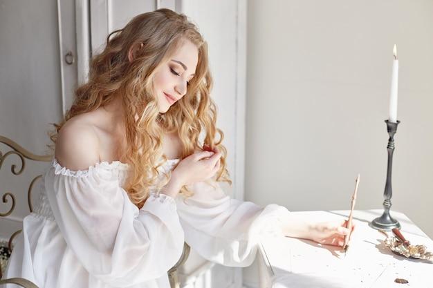 소녀는 하얀 빛 드레스, 순수함과 순수함으로 집에 앉아있는 사랑하는 남자에게 편지를 씁니다. 곱슬 금발의 낭만적 인 모습