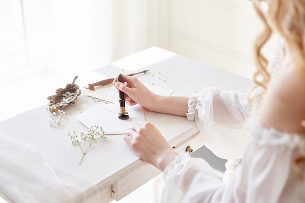 Girl writes letter her beloved man sitting table