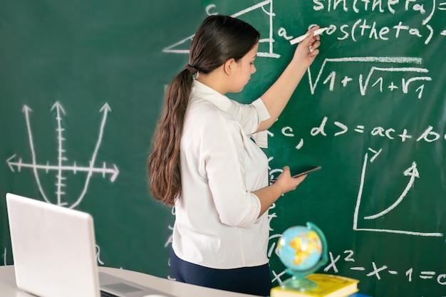 Девушка пишет математические примеры на школьной доске решает геометрическую задачу