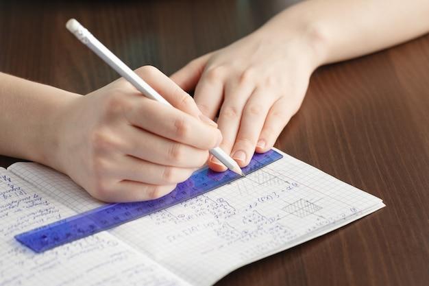 Girl writes in a notebook mathematical formulas
