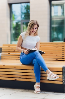 Girl writes in a notebook, sitting on a bench in the park.
