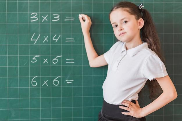 Girl writing calculation on blackboard