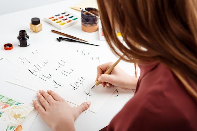 Девушка написание каллиграфии на открытках. арт дизайн.