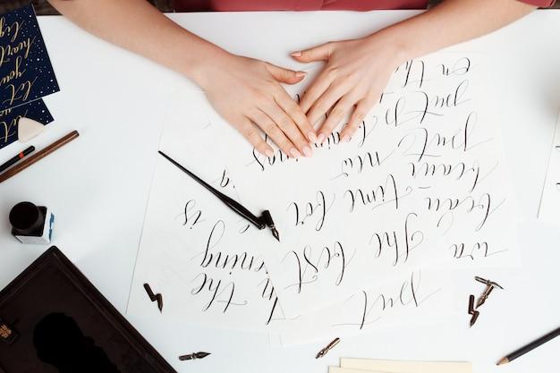 Girl writing calligraphy on postcards. art design. above.