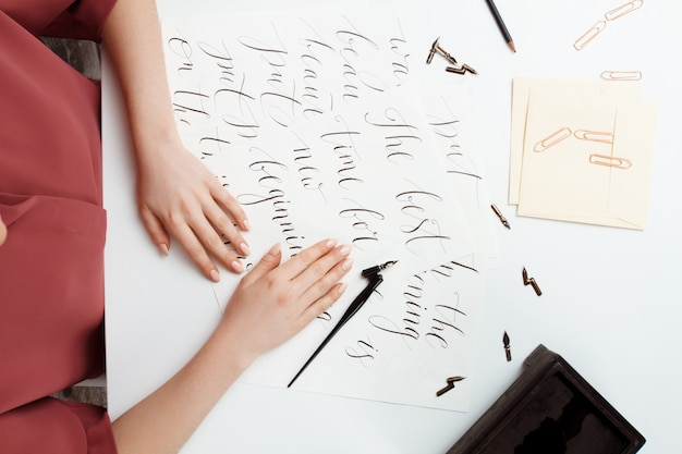 Girl writing calligraphy on postcards. art design. above.