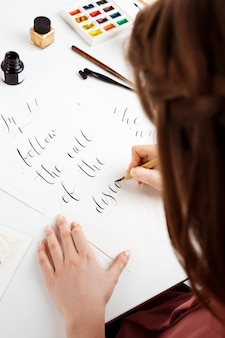 Girl writing calligraphy on postcards. art design.