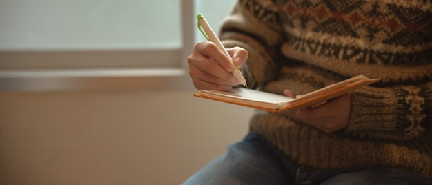 A girl writing on diary notebook while sitting at reading corner beside window