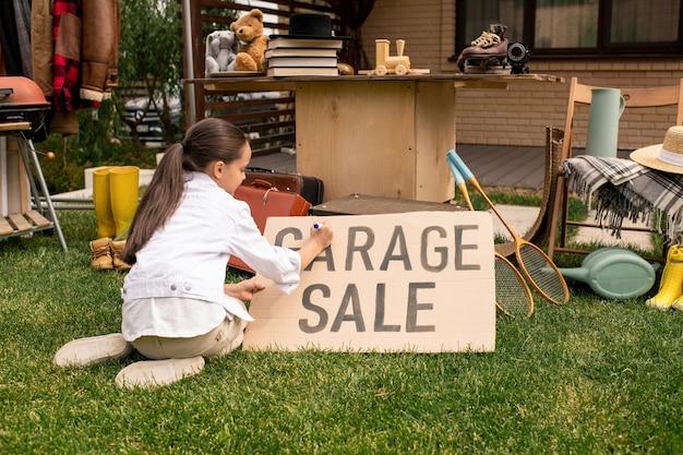 Girl writing garage sale on banner