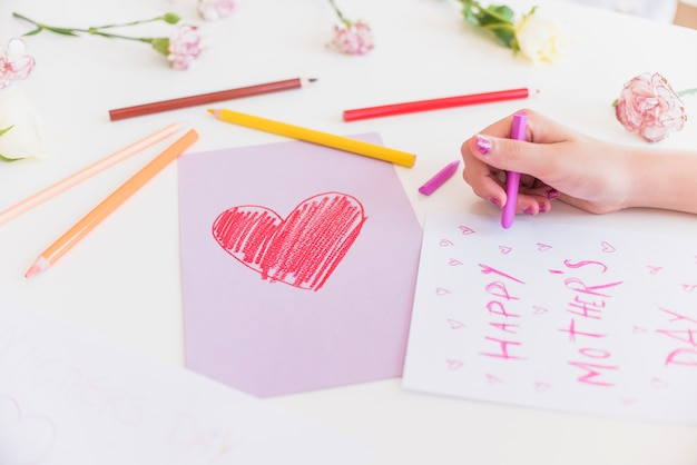 Girl writing happy mothers day on paper sheet