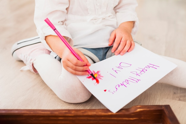 Girl writing happy mothers day on paper