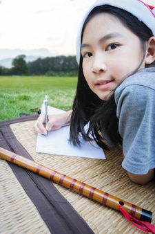 Girl writing how to learning flute, laying grass ground