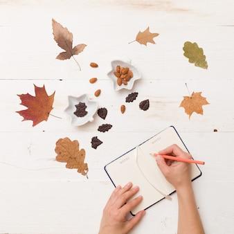 Девушка пишет в блокноте на белом деревянном столе с листьями шоколада и орехами