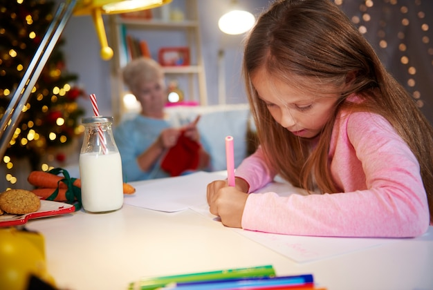 Girl writing a letter to santa in christmas season