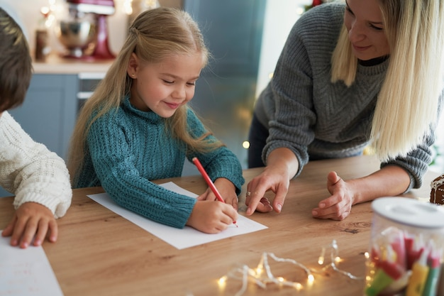 Girl writing a letter to santa claus with her mom