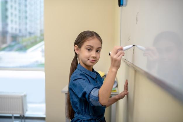 Девушка пишет на доске маркером